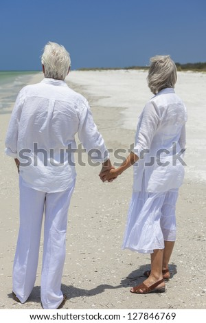 Rear view of happy senior man and woman couple holding hands together looking out to sea on a deserted tropical beach with bright clear blue sky. - stock photo
