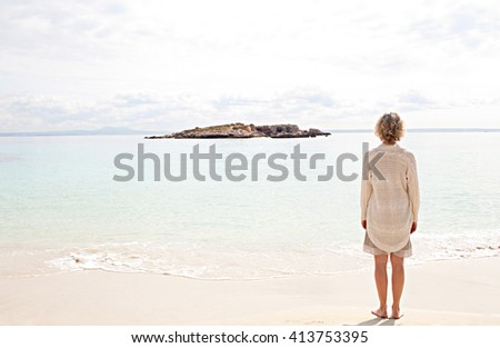Rear view of healthy senior woman standing on a clear beach shore contemplating the sea, relaxing on a sunny holiday destination natural beach, sunny outdoors. Travel and lifestyle, vacation exterior. - stock photo