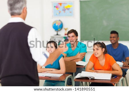 rear view of high school teacher teaching students in classroom