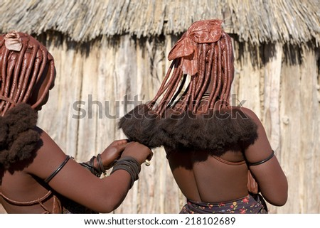 Rear view of himba women that make each other the traditional hairstyle of Himba