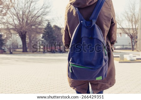 Rear view of hipster girl carring backpack on her back, copyspace - stock photo