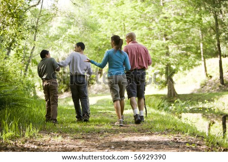 Rear view of Hispanic family walking along trail in park, boys 10 and 14 years old - stock photo