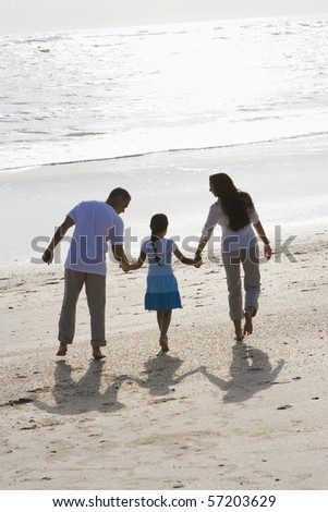 Rear view of Hispanic family with 9 year old girl holding hands walking on beach - stock photo