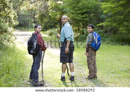 Rear view of Hispanic father and two sons (10 and 14 years) hiking on path in woods - stock photo