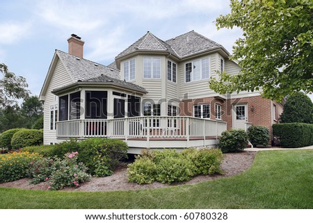 Rear view of home with enclosed porch - stock photo