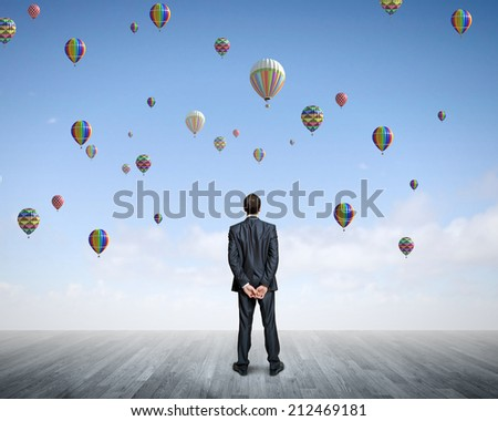 Rear view of hopeful businessman looking at balloons flying in sky