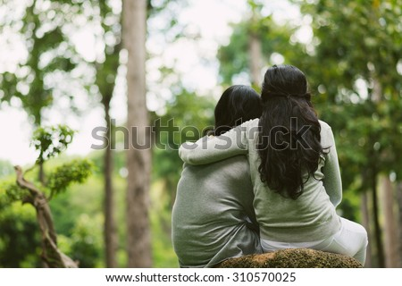 Rear view of hugging female friends sitting in the park - stock photo