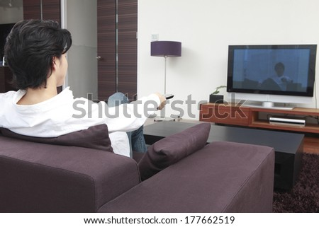 Rear View of Japanese man and TV with the remote control
