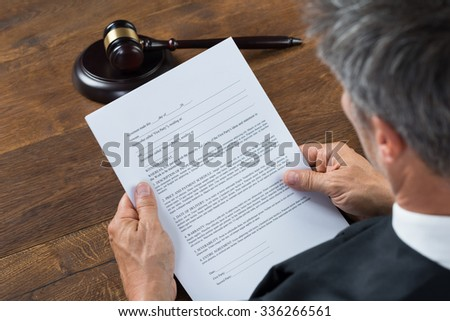 Rear view of judge reading document at table in courtroom - stock photo