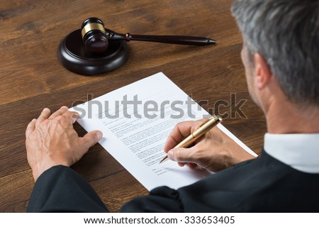 Rear view of judge writing on paper at table in courtroom - stock photo