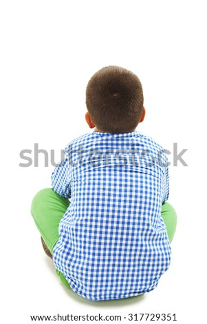 Rear view of little boy sitting on floor. Isolated on white background - stock photo