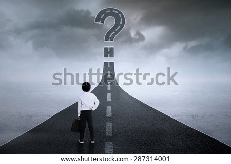 Rear view of little entrepreneur standing on the highway while looking at a question sign - stock photo