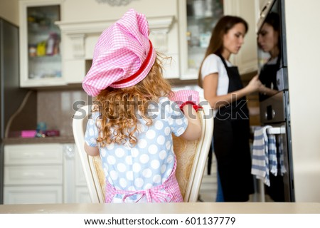 Rear view of little girl in kitchen with mother