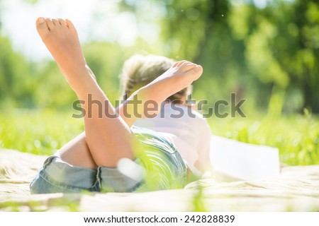 Rear view of little girl lying in summer park - stock photo