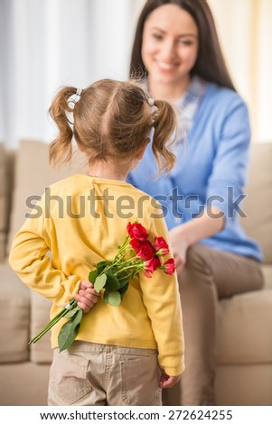 Rear view of little girl with bunch of beautiful roses behind back preparing nice surprise for her mother. - stock photo