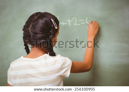 Rear view of little girl writing on blackboard in the classroom - stock photo