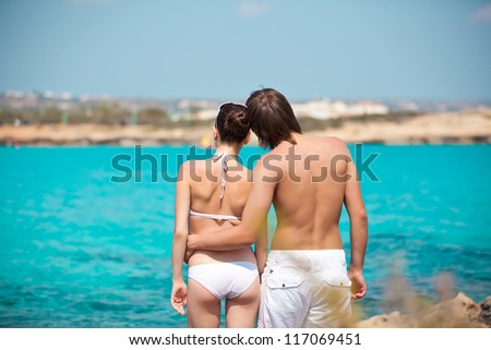 Rear view of lovely young couple standing on the beach facing sea - stock photo