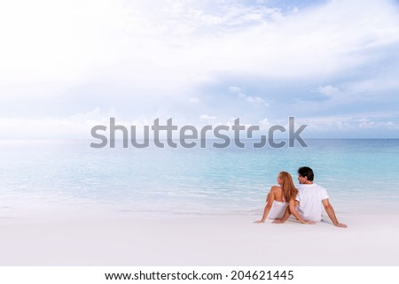 Rear view of loving couple relaxing on the beach, boyfriend with girlfriend enjoying summer holidays on luxury Maldives resort, love and romance concept  - stock photo