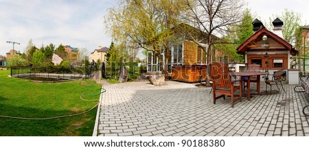 Rear view of luxury home backyard with swimming pool, patio and lawn - stock photo