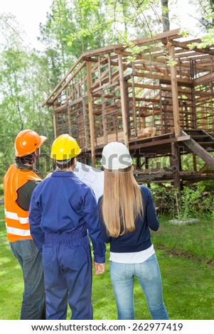 Rear view of male and female architects with blueprint examining incomplete wooden cabin at site - stock photo
