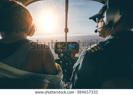 Rear view of male and female pilots flying a helicopter on sunny day. Man flying a helicopter with his copilot looking outside the aircraft. - stock photo