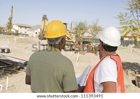 Rear view of male architects with blueprint at construction site - stock photo