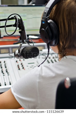 Rear view of male dj working in front of a microphone on the radio - stock photo