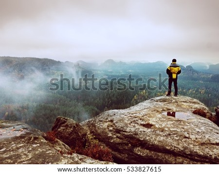 Rear view of male hiker in yellow black jacket on rocky peak while enjoying a daybreak above mountains valley