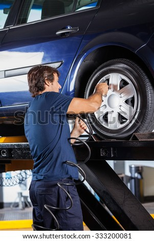 Rear view of male mechanic refilling car tire at auto repair shop - stock photo