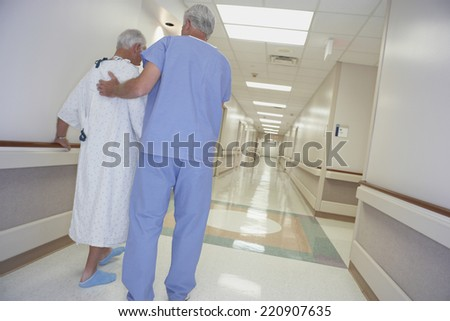 Rear view of male nurse helping senior patient walk in corridor - stock photo