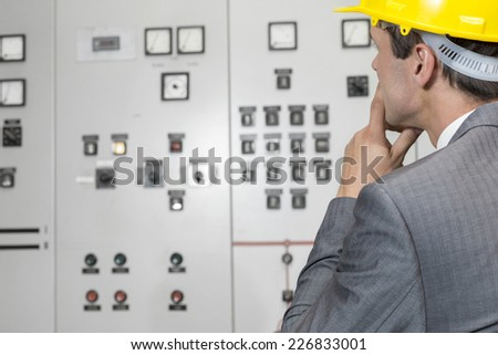 Rear view of male supervisor examining control room in industry - stock photo