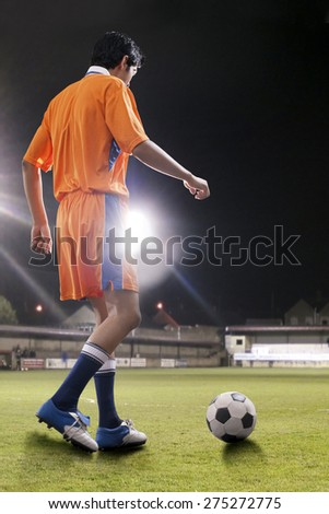 Rear view of man about to kick ball at soccer field - stock photo