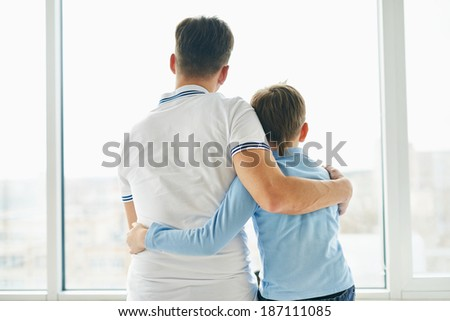 Rear view of man and his son embracing one another and looking through window - stock photo