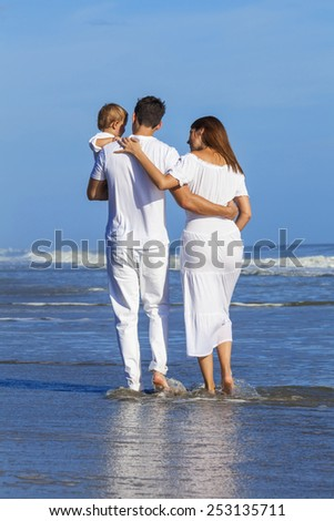 Rear view of man and woman boy child couple family in white clothes happy walking on an empty beach with bright clear blue sky  - stock photo