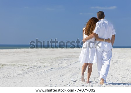 Rear view of man and woman romantic couple in white clothes walking on a deserted tropical beach with bright clear blue sky - stock photo