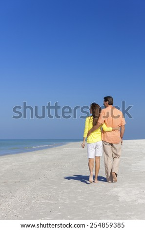 Rear view of man and woman romantic couple walking on a deserted tropical beach with bright clear blue sky - stock photo