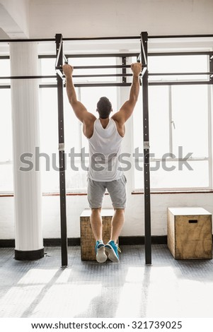 Rear view of man doing pull ups at the gym - stock photo