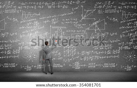 Rear view of man drawing formulas on blackboard with chalk - stock photo