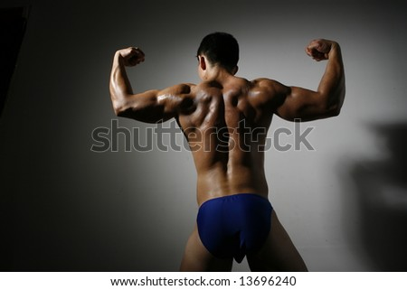 Rear view of man flexing