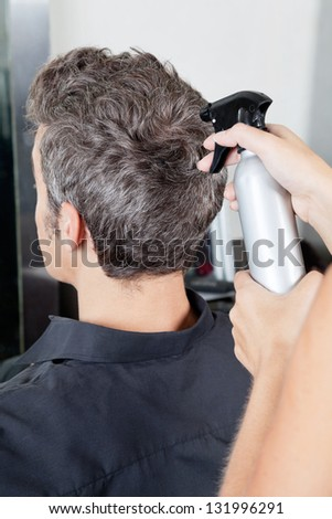 Rear view of man getting a haircut in beauty salon - stock photo