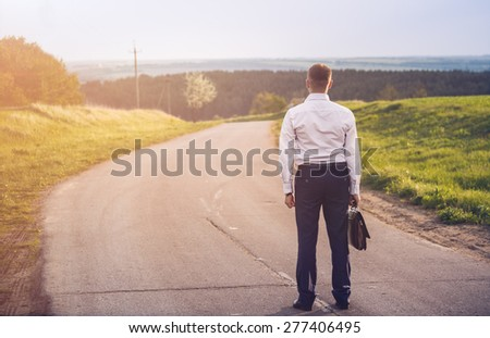 Rear view of man on country road. Vintage toning - stock photo