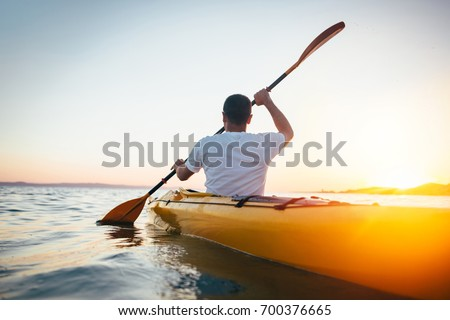 Rear view of man paddling canoe. Paddling, canoeing, kayaking