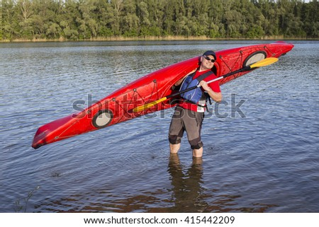 Rear view of man paddling kayak in lake with woman in background. Couple kayaking in lake on a sunny day. - stock photo