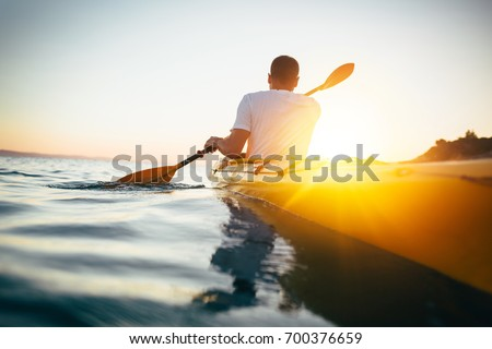 Rear view of man paddling kayak. Paddling the canoe at sunset. Kayaking, canoeing, paddling