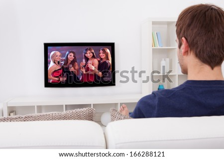 Rear View Of Man Watching Television At Home - stock photo