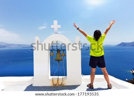 Rear view of man with arms outstretched standing next to the religion's bells and looking at seascape - stock photo