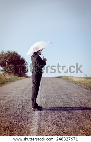 Rear view of man with white umbrella looking away on the road - stock photo