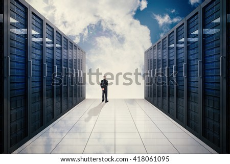 Rear view of mature businessman posing against server hallway in the sky