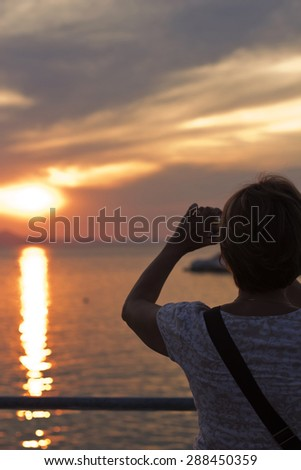 Rear  view  of mature woman enjoying sunset by the sea and taking photo  with smart phone. - stock photo