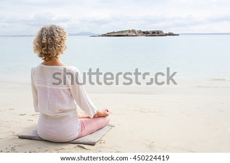 Rear view of mature woman in holiday destination beach contemplating blue sea sitting on shore in yoga position, meditating outdoors. Well being mature sport and healthy lifestyle, nature exterior. - stock photo